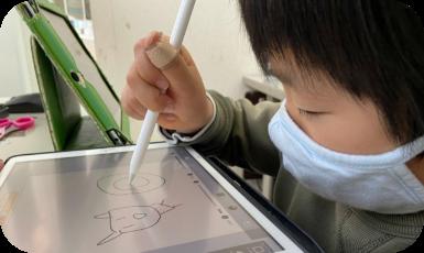 タブレットで絵を描いている児童